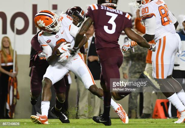 Cornerback Adonis Alexander of the Virginia Tech Hokies hits wide receiver Deon Cain of the Clemson Tigers following his reception in the first half...