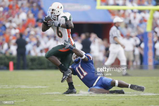 Cornerback Antrel Rolle of the University of Miami drags wide receiver OJ Small of the University of Florida behind him after during the NCAA...