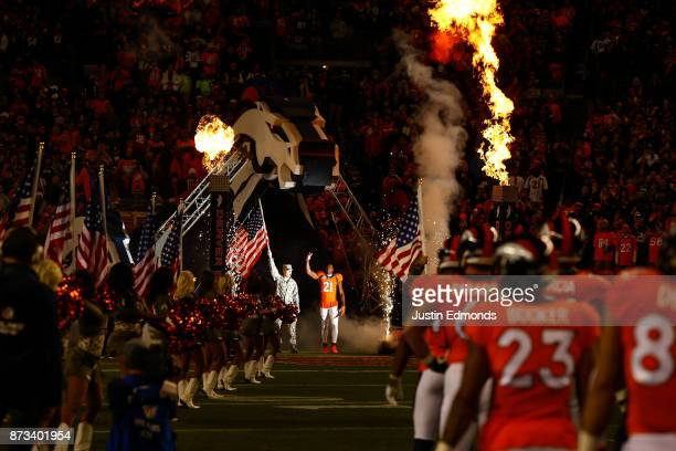 Cornerback Aqib Talib of the Denver Broncos walks onto the field next to a member of the armed forces during player introductions before a game...
