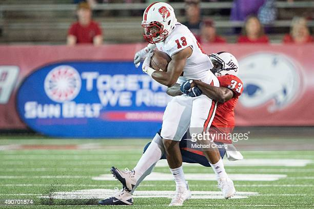 Cornerback Berron Tyson of the South Alabama Jaguars attempts to tackle wide receiver Bra'Lon Cherry of the North Carolina State Wolfpack on...