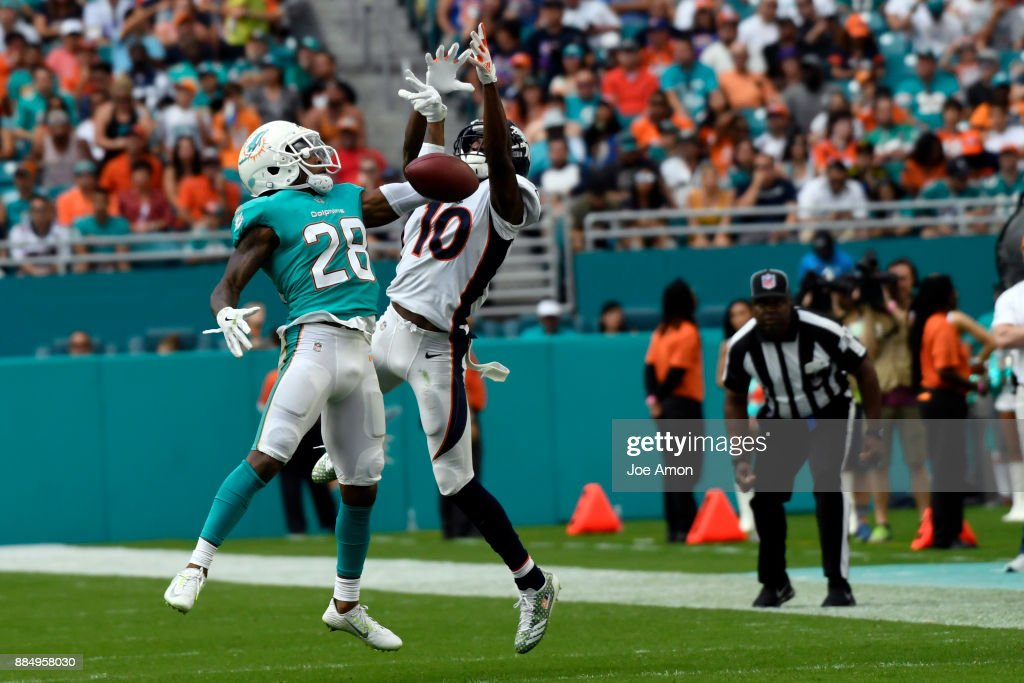 Cornerback Bobby McCain #28 of the Miami Dolphins breaks up a pass to wide receiver Emmanuel Sanders #10 of the Denver Broncos as the Broncos lose 35-9 to the Miami Dolphins at Hard Rock Stadium in Miami Gardens, Florida December 3, 2017.