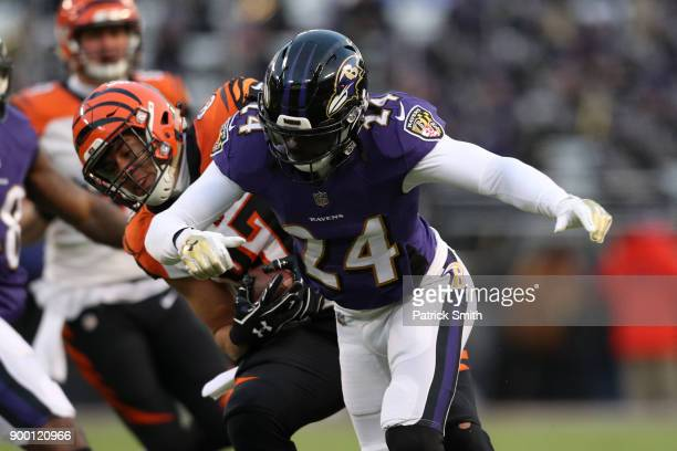 Cornerback Brandon Carr of the Baltimore Ravens tackles tight end CJ Uzomah of the Cincinnati Bengals in the first quarter at MT Bank Stadium on...