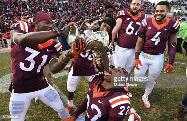 Cornerback Brandon Facyson of the Virginia Tech Hokies pours water from the Commonwealth Cup into the mouth of rover Terrell Edmunds following the...