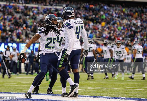 Cornerback Byron Maxwell of the Seattle Seahawks celebrates with teammate cornerback Richard Sherman after Maxwell's interception during the 2nd half...
