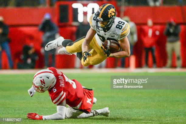 Cornerback Cam TaylorBritt of the Nebraska Cornhuskers upends wide receiver Nico Ragaini of the Iowa Hawkeyes at Memorial Stadium on November 29 2019...