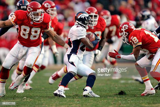 Cornerback Champ Bailey of the Denver Broncos runs with an interception against tight end Tony Gonzalez and wide receiver Sammie Parker of the Kansas...