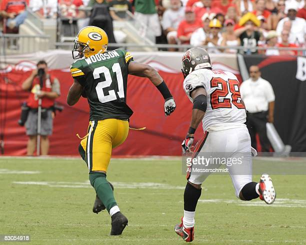 Cornerback Charles Woodson of the Green Bay Packers wrestles a pass away from running back Warrick Dunn of the Tampa Bay Buccaneers at Raymond James...