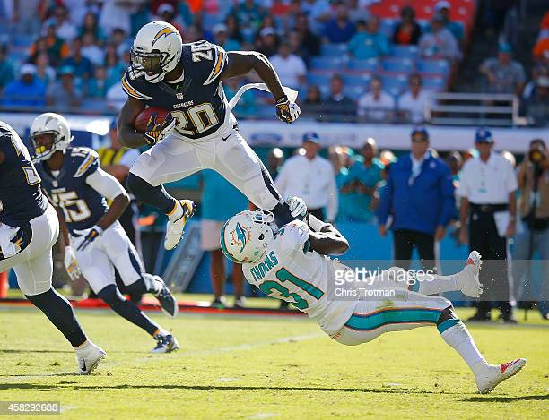 Cornerback Chris Davis of the San Diego Chargers is brought down by free safety Michael Thomas of the Miami Dolphins in the second half during a game...