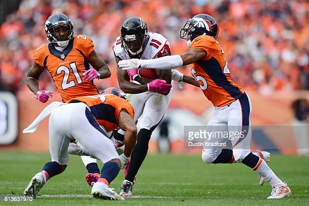 Cornerback Chris Harris and strong safety TJ Ward of the Denver Broncos tackle wide receiver Julio Jones of the Atlanta Falcons after he got a first...