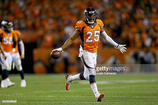 Cornerback Chris Harris of the Denver Broncos celebrates as he intercepts a pass thrown by quarterback Cam Newton of the Carolina Panthers in the...