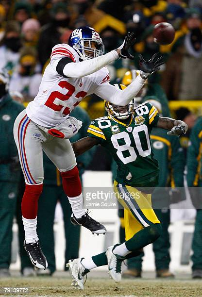 Cornerback Corey Webster of the New York Giants intercepts a Brett Favre of the Green Bay Packers pass in front of Donald Driver of the Packers in...