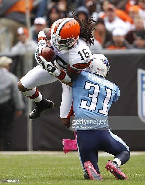 Cornerback Cortland Finnegan of the Tennessee Titans tackles wide receiver Joshua Cribbs of the Cleveland Browns at Cleveland Browns Stadium on...