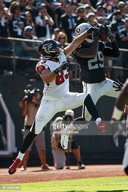 Cornerback David Amerson of the Oakland Raiders intercepts a pass intended for tight end Jacob Tamme of the Atlanta Falcons during the third quarter...