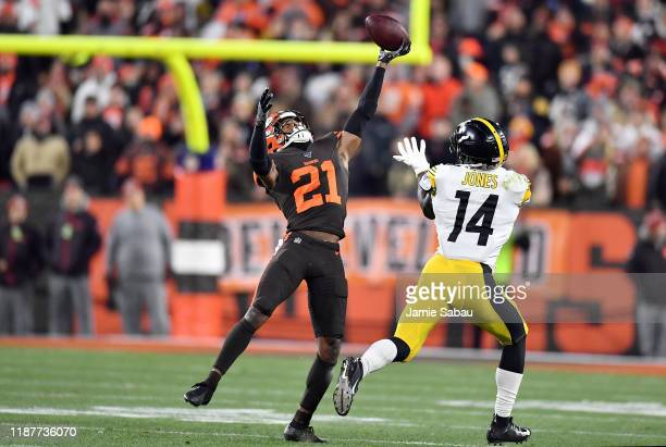 Cornerback Denzel Ward of the Cleveland Browns tips the ball to teammate Morgan Burnett for an interception in the second quarter of the game against...