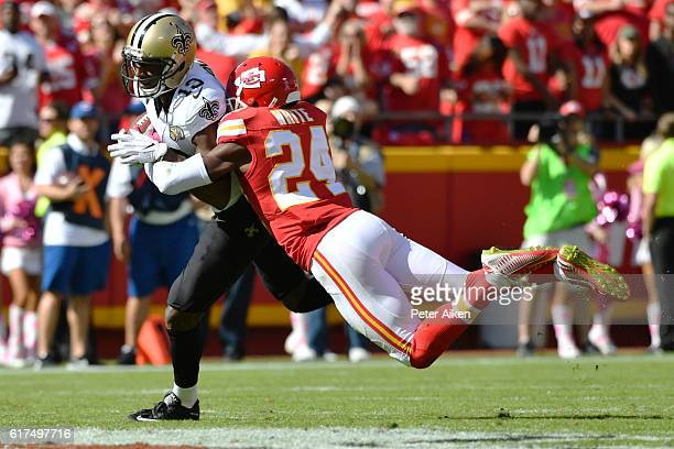 Cornerback D.J. White of the Kansas City Chiefs dives to tackle wide receiver Michael Thomas of the New Orleans Saints at Arrowhead Stadium during...