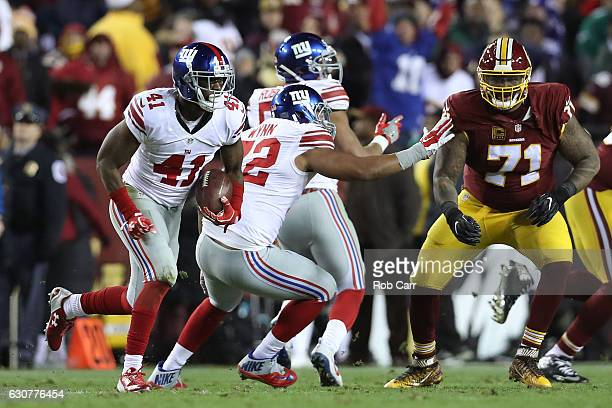 Cornerback Dominique RodgersCromartie of the New York Giants returns the ball against tackle Trent Williams of the Washington Redskins after...