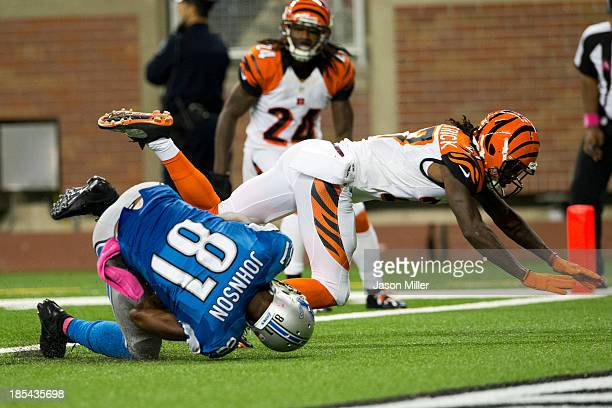 Cornerback Dre Kirkpatrick of the Cincinnati Bengals tackles wide receiver Calvin Johnson of the Detroit Lions as Johnson lands in the end zone for a...