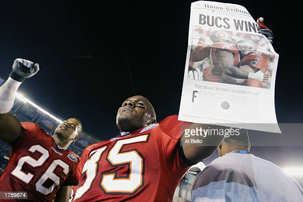 Cornerback Dwight Smith of the Tampa Bay Buccaneers celebrates as teammate Corey Ivy holds a newspaper proclaiming that his team defeated the Oakland...