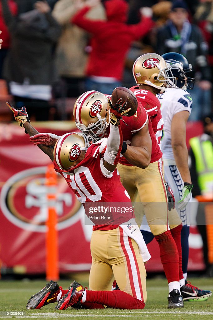 Cornerback Eric Wright #31 of the San Francisco 49ers celebrates his interception with safety Eric Reid #35 to seal the game against the Seattle Seahawks with under a minute left in the fourth quarter on December 8, 2013 at Candlestick Park in San Francisco, California. The 49ers won 19-17.