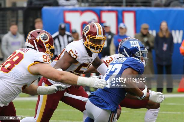 Cornerback Fabian Moreau Defensive Lineman Matt Ioannidis and Linebacker Zach Brown of the Washington Redskins make a stop against the New York...