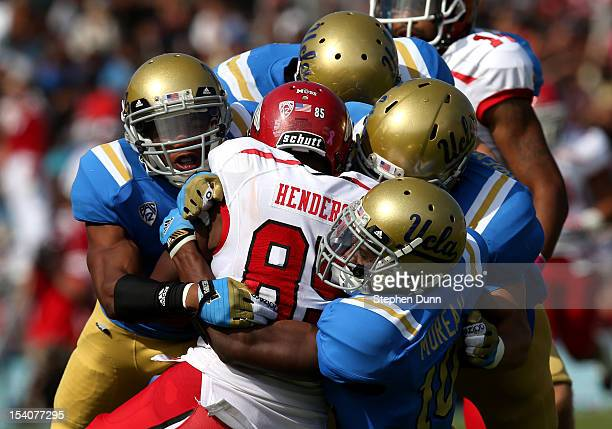 Cornerback Fabian Moreau of the UCLA Bruins leads a swarm of Bruins as they tackle wide receiver Charles Henderson of the Utah Utes at the Rose Bowl...