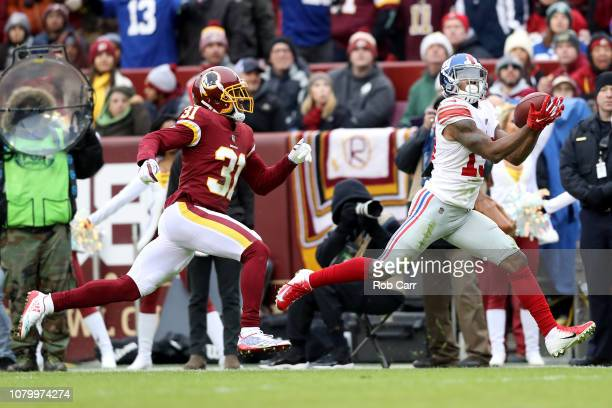 Cornerback Fabian Moreau of the Washington Redskins looks on as wide receiver Corey Coleman catches a first half pass at FedExField on December 09...