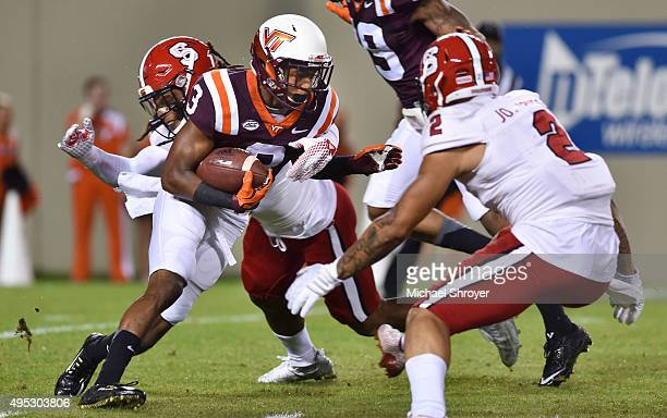 Cornerback Greg Stroman of the Virginia Tech Hokies is hit by nickelback Dravious Wright of the North Carolina State Wolfpack during a punt return in...