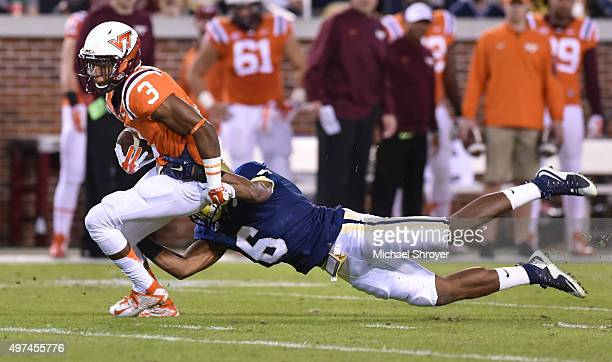 Cornerback Greg Stroman of the Virginia Tech Hokies is tackled by defensive back Chris Milton of the Georgia Tech Yellow Jackets in the first half at...