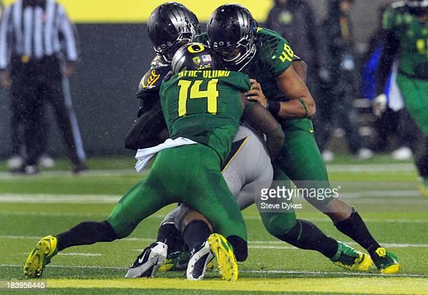 Cornerback Ifo EkpreOlomu of the Oregon Ducks and linebacker Rodney Hardrick of the Oregon Ducks tackle running back Brendan Bigelow of the...