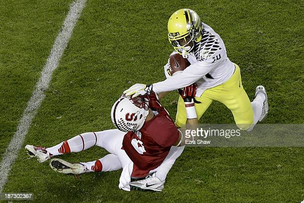 Cornerback Ifo EkpreOlomu of the Oregon Ducks intercepts a pass to wide receiver Michael Rector of the Stanford Cardinal but is called for passing...