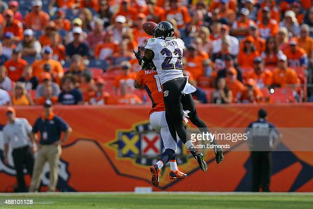 Cornerback Jimmy Smith of the Baltimore Ravens breaks up a pass intended for wide receiver Jordan Norwood of the Denver Broncos before intercepting...