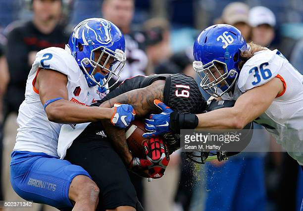 Cornerback Jonathan Moxey and linebacker Tyler Gray of the Boise State Broncos tackle wide receiver Kenny Golladay of the Northern Illinois Huskies...