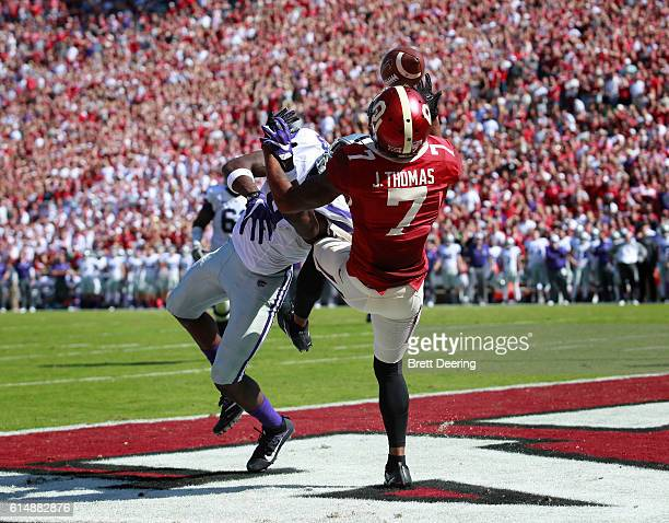 Cornerback Jordan Thomas of the Oklahoma Sooners breaks up and tries to catch a pass intended for wide receiver Byron Pringle of the Kansas State...