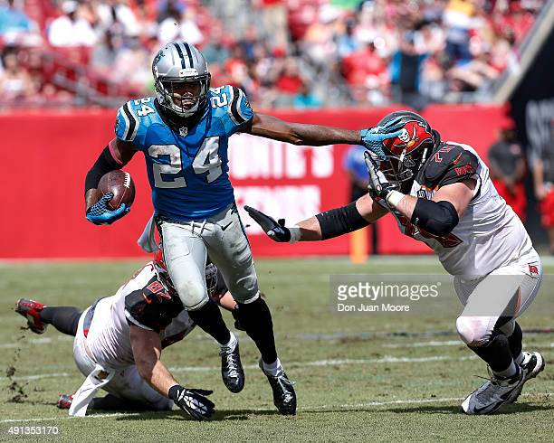 Cornerback Josh Norman of the Carolina Panthers stiif arms Guard Logan Mankins of the Tampa Bay Buccaneers on a run back from his second interception...