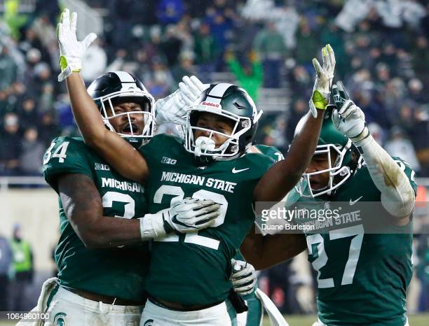 Cornerback Josiah Scott celebrates with linebacker Antjuan Simmons and safety Khari Willis of the Michigan State Spartans after intercepting a pass...