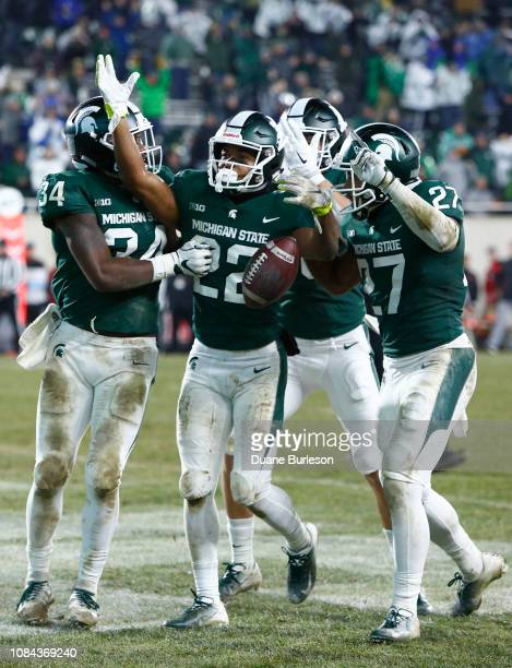 Cornerback Josiah Scott of the Michigan State Spartans celebrates with linebacker Antjuan Simmons of the Michigan State Spartans and safety Khari...