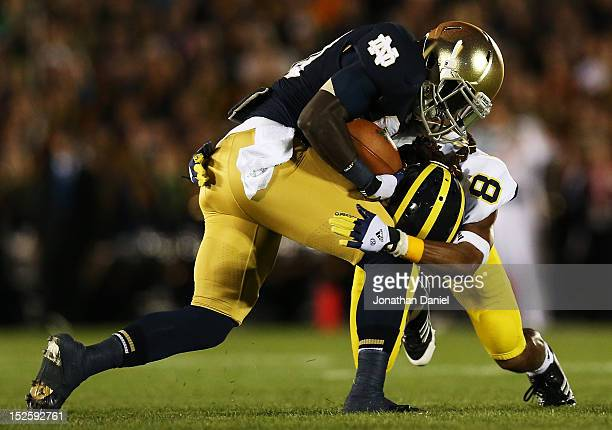 Cornerback JT Floyd of the Michigan Wolverines tackles running back Cierre Wood of the Notre Dame Fighting Irish in the first quarter at Notre Dame...