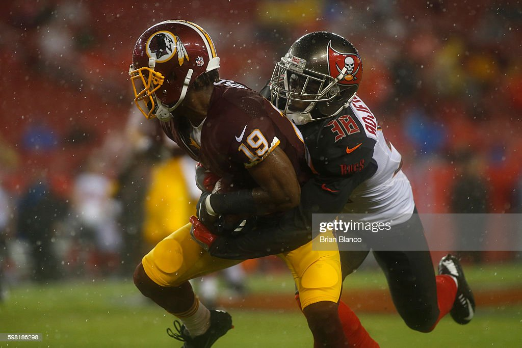 Cornerback Jude Adjei-Barimah #38 of the Tampa Bay Buccaneers brings down wide receiver Rashad Ross #19 of the Washington Redskins during the first quarter of an NFL game on August 31, 2016 at Raymond James Stadium in Tampa, Florida.