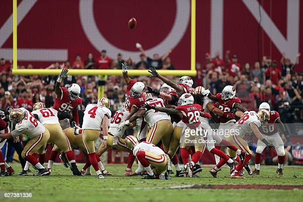 Cornerback Justin Bethel of the Arizona Cardinals and nose tackle Corey Peters attempt to block a field goal by kicker Phil Dawson of the San...