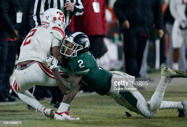 Cornerback Justin Layne of the Michigan State Spartans tackles running back Raheem Blackshear of the Rutgers Scarlet Knights during the second half...