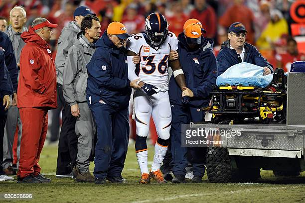 Cornerback Kayvon Webster of the Denver Broncos is helped off the field after an injury during the game against the Kansas City Chiefs at Arrowhead...