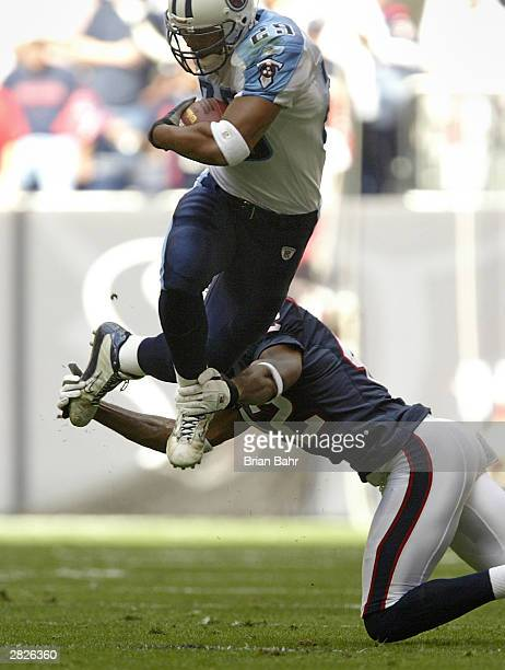 Cornerback Marcus Coleman of the Houston Texans trips up running back Chris Brown of the Tennessee Titans December 21 2003 at Reliant Stadium in...