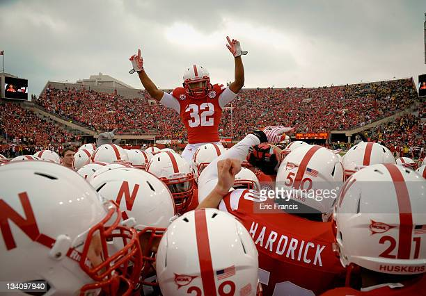 Cornerback Marcus Mendoza of the Nebraska Cornhuskers jumps atop a pre game scrum as the Nebraska Cornhuskers prepare to plan the Iowa Hawkeyes at...