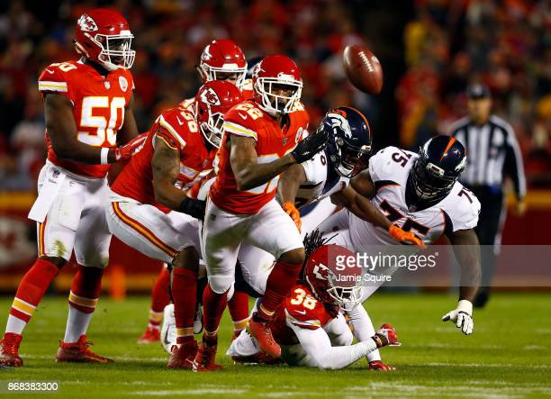 Cornerback Marcus Peters of the Kansas City Chiefs forces a fumble by running back Jamaal Charles of the Denver Broncos during the game at Arrowhead...