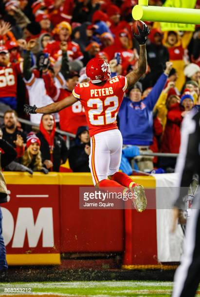 Cornerback Marcus Peters of the Kansas City Chiefs goes up to dunk the football over the goal post after returning a fumble for a touchdown against...