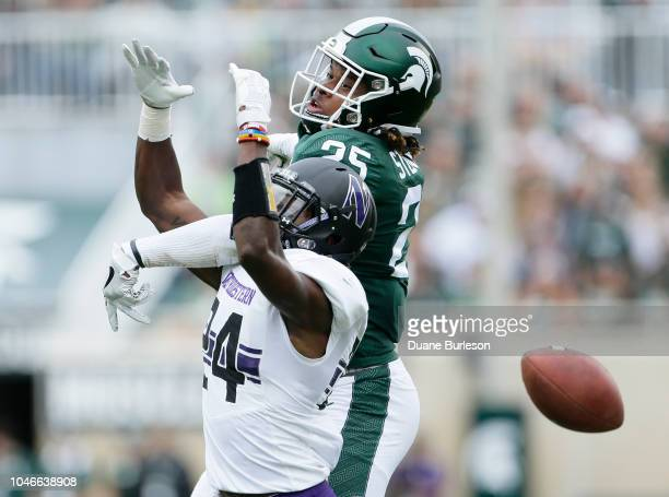 Cornerback Montre Hartage of the Northwestern Wildcats breaks up a pass intended for wide receiver Darrell Stewart Jr #25 of the Michigan State...