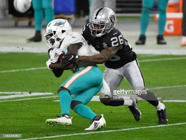 Cornerback Nevin Lawson of the Las Vegas Raiders tackles wide receiver Jakeem Grant of the Miami Dolphins after he got a first down on a pass play in...