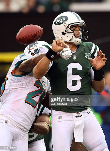 Cornerback Nolan Carroll of the Miami Dolphins forces quarterback Mark Sanchez of the New York Jets to fumble at MetLife Stadium on October 28 2012...
