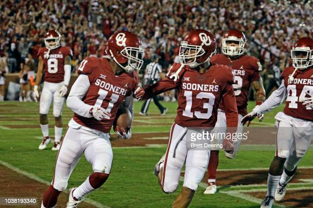 Cornerback Parnell Motley and cornerback Tre Norwood of the Oklahoma Sooners celebrate an interception and the end of overtime against the Army Black...