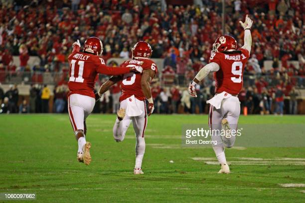 Cornerback Parnell Motley cornerback Tre Brown and linebacker Kenneth Murray of the Oklahoma Sooners celebrate stopping the Oklahoma State Cowboys on...